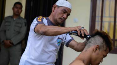 Polisi saat mencukur rambut salah satu anak Punk di Banda Aceh (9/1). Sebanyak 30 orang anak Punk ditahan oleh Polisi Syariah di Aceh. (AFP Photo/Chaideer Mahyuddin)