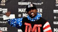 Petinju AS, Floyd Mayweather Jr, memamerkan cek bernilai 100 juta dolar pada konferensi pers menjelang duel kontra Conor McGregor di Staples Center, Selasa (11/7/2017) malam waktu setempat. (AFP/Gene Blevins)