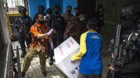 Pekerja menurunkan vaksin COVID-19 produksi Sinovac dari truk pengawalan polisi di Surabaya pada Senin (4/1/2021).  Pemerintah mulai mendistribusikan 3 juta dosis vaksin Covid-19 asal perusahaan China, Sinovac, ke 34 provinsi Indonesia. (Photo by Juni Kriswanto / AFP)