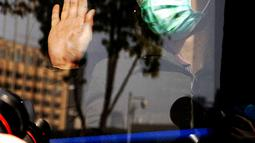 Pasien virus corona yang pulih melambaikan tangan kepada pekerja medis ketika meninggalkan rumah sakit sementara Wuchang di Wuhan, Hubei, China (10/3/2020). Kelompok terakhir yang terdiri dari 49 pasien meninggalkan rumah sakit pada Selasa (10/3) pukul 15.30 waktu setempat. (Xinhua/Wang Yuguo)