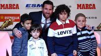 Megabintang Barcelona, Lionel Messi berpose dengan anak-anak dari rumah sakit de Joan de Deu setelah menerima trofi Sepatu Emas Eropa kelimanya dalam sebuah acara di Antiga Fabrica Estrella Damm, Selasa (18/12). (LLUIS GENE/AFP)