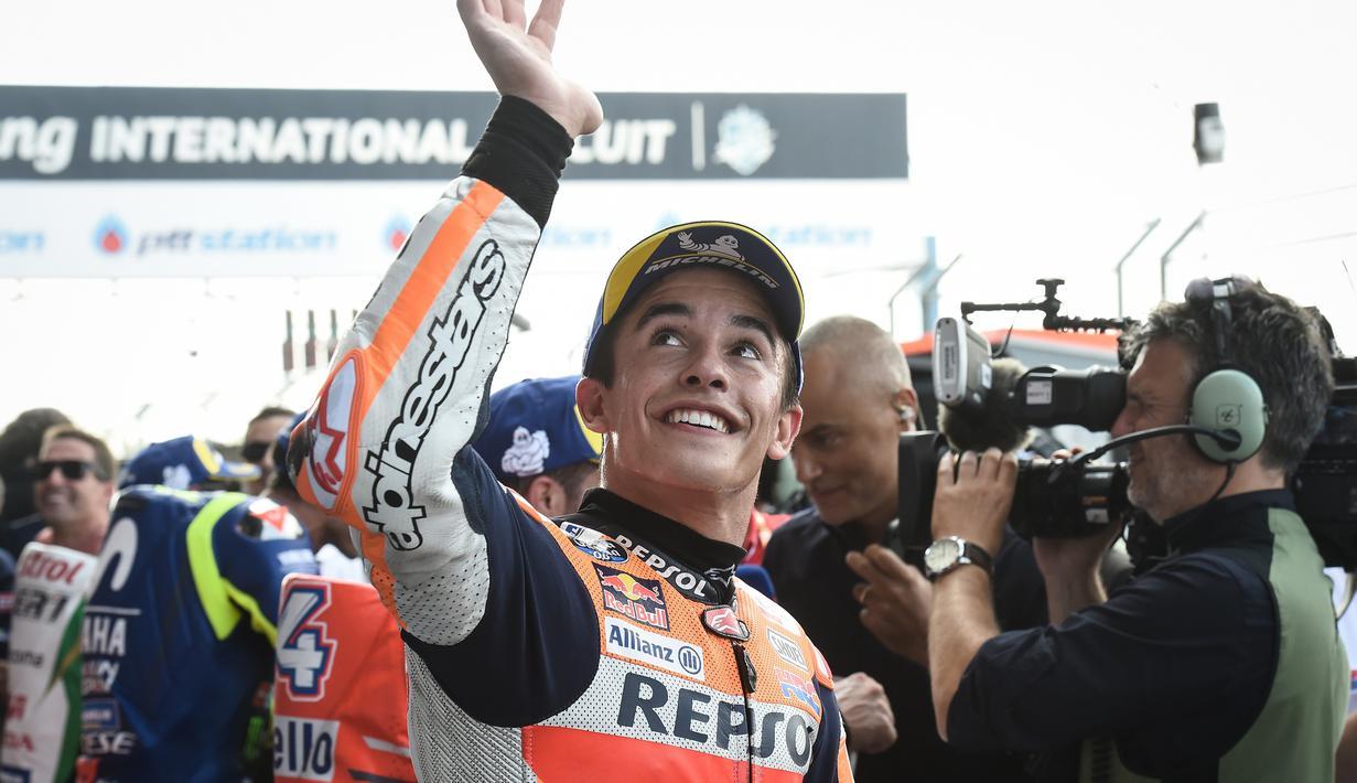 Pebalap tim MotoGP Repsol Honda Marc Marquez tersenyum saat menyapa fans setelah kualifikasi MotoGP Thailand 2018 di Sirkuit Internasional Buriram (6/10). Marquez menorehkan waktu tercepat dengan catatan waktu 1.30.088. (AFP Photo/Lillian Suwanrmpha)