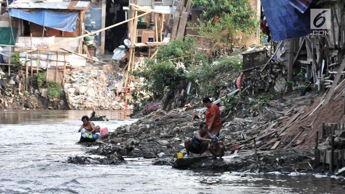 Warga memandikan anaknya di bantaran Kali Ciliwung, Jakarta, Senin (19/11). Saat ini, tercatat sekitar 500 ribu penduduk DKI Jakarta tidak memiliki akses sanitasi yang layak. (Merdeka.com/Iqbal Nugroho)