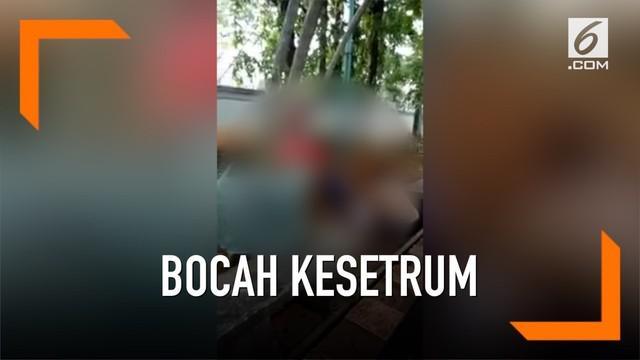 Seorang bocah terkapar tak berdaya karena kesetrum. Tangannya tak sengaja memegang tiang listik di kolam renang Kompleks Perumahan Villa Meruya, Jakarta Barat.