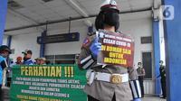 Seorang Polwan Direktorat Lalu Lintas Polda Jawa Tengah menunjukkan poster Cegah Covid-19 saat sterilisasi puluhan angkutan bus yang masuk di Terminal Bawen, Jumat (27/3/2020). (Liputan6.com/Gholib)