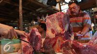 Pedagang memotong daging sapi yang dijualnya di Pasar Senen, Jakarta, Jumat (5/8). Pemerintah mencabut ketentuan kewajiban importir daging untuk menyerap daging lokal sebanyak tiga persen dari total kuota impor yang diperoleh. (Liputan6.com/Angga Yuniar)
