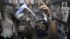 Pedagang merapikan alat pelindung wajah atau face shield di salah satu kios Pasar Pramuka, Jakarta, Rabu (3/6/2020). Jelang pemberlakuan new normal, penjualan face shield meningkat dalam beberapa hari terakhir. (merdeka.com/Iqbal S. Nugroho)