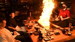 Pengunjung menikmati hidangan teppanyaki Jepang di Chinatown, Melbourne, Australia, Jumat (22/10/2021). Melbourne melonggarkan kebijakan lockdown mulai hari ini setelah berlangsung lebih dari 260 hari. (William WEST/AFP)