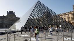 """Pengunjung tiba di piramida Louvre yang dirancang arsitek China Ieoh Ming Pei, pintu masuk ke Museum Louvre di Paris (6/7/2020). Presiden dan direktur Louvre Jean-Luc Martinez mengatakan, krisis coronavirus telah menyebabkan """"lebih dari 40 juta euro dalam kerugian di Louvre. (AFP/Francois Guillot)"""