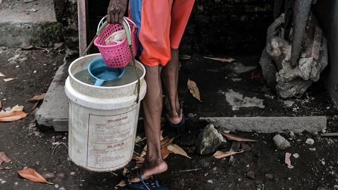 Warga membawa air yang diambil dari sumur timba di kawasan Sukapura, Cilincing, Jakarta, Senin (22/3/2021) (merdeka.com/Iqbal S. Nugroho)