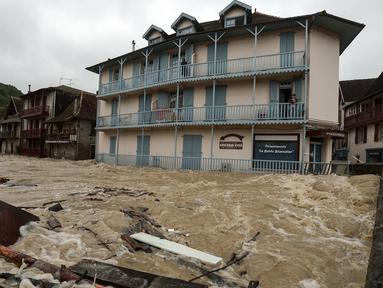 Warga berdiri di balkon lantai atas sebuah gedung menyaksikan banjir merendam jalanan setelah hujan lebat di Salies-de-Bearn, Prancis barat daya (13/6). (AFP Photo/Iroz Gaizka)