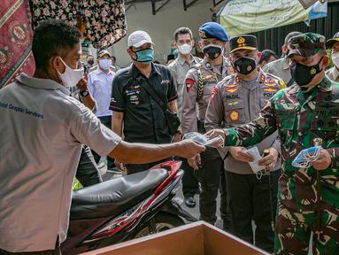 Pangdam Jaya Mayjen TNI Dudung Abdurrachman (kanan) dan Kapolda Metro Jaya Irjen Pol Fadil Imran membagikan masker kepada warga di Sunter Muara, Tanjung Priok, Jakarta, Selasa (9/2/2021). Kegiatan ini untuk menyadarkan masyarakat akan pentingnya penggunaan masker. (Liputan6.com/Faizal Fanani)