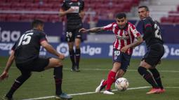 Striker Atletico Madrid, Angel Correa (kedua dari kanan) melewati bek Eibar untuk mencetak gol kedua timnya ke gawang Eibar dalam laga lanjutan Liga Spanyol 2020/2021 pekan ke-31 di Wanda Metropolitano Stadium, Madrid, Minggu (18/4/2021). Atletico menang 5-0 atas Eibar. (AP/Bernat Armangue)