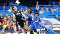 Penyerang Chelsea, Michy Batshuayi, duel udara dengan pemain Brighton & Hove Albion, Lewis Dunk, pada laga Premier League di Stadion Stamford Bridge, Sabtu (28/9). Chelsea menang 2-0. (AP/Frank Augstein)