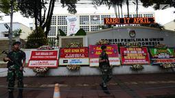Tentara bersenjata berjaga dekat karangan bunga yang ada di Gedung Komisi Pemilihan Umum (KPU), Jakarta, Sabtu (20/4). Karangan bunga tersebut merupakan dukungan masyarakat kepada KPU untuk terus berkerja maksimal dalam menghitung suara Pilpres 2019. (merdeka.com/Imam Buhori)