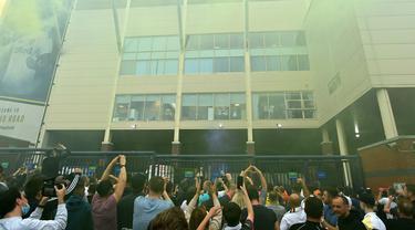 Para pemain Leeds United di sebuah jendela di dalam stadion menyapa pendukung mereka untuk merayakan kembalinya klub ke Liga Premier setelah 16 tahun, di Leeds, Inggris utara (17/7/2020). Leeds United memastikan diri tampil di Premier League musim depan (2020/2021). (AFP/Paul Ellis)