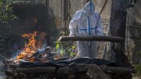 Kerabat seseorang yang meninggal karena COVID-19 melakukan ritual saat kremasi di Gauhati, India, pada Selasa (27/4/2021). Kasus virus corona COVID-19 di India melonjak lebih cepat dari tempat lain di dunia. (AP Photo/Anupam Nath)