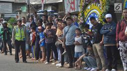 Warga sekitar Puri Cikeas bersiap menyambut iring-iringan kepergian jenazah Ani Yudhoyono menuju TMP Kalibata, Bogor, Jawa Barat, Minggu (2/6/2019). Ani Yudhoyono dimakamkan di samping pusara istri presiden ke-3 RI BJ Habibie, Ainun Habibie. (Liputan6.com/Immanuel Antonius)