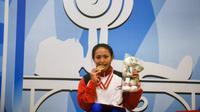Atlet Bali, Ni Nengah Widiasih, menggigit medali emas usai menjadi juara pada pada kelas 41 kg putri cabang olahraga angkat berat Peparnas 2016 di Hotel Preanger, Bandung, Jawa Barat, Selasa (18/10/2016) (pon-peparnas2016jabar.go.id)
