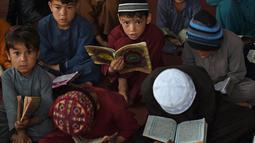 Anak-anak membaca Alquran selama bulan suci Ramadhan di sebuah masjid di pinggiran Kabul, Afghanistan, Selasa (27/4/2021).  Bulan Ramadhan menjadi momen untuk memperbanyak amalan, termasuk ketekunan menjalani tadarus Alquran. (WAKIL KOHSAR / AFP)