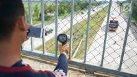Petugas mengoperasikan alat pengukur kecepatan (speed gun) kendaraan di sekitar Gerbang Tol Palimanan, Cirebon, Jawa Barat, Jumat (7/6/2019). Hal itudilakukan setiap satu jam sekali untuk mengetahui tingkat kepadatan lalu lintas di sepanjang jalur tol Trans Jawa. (Liputan6.com/Immanuel Antonius)