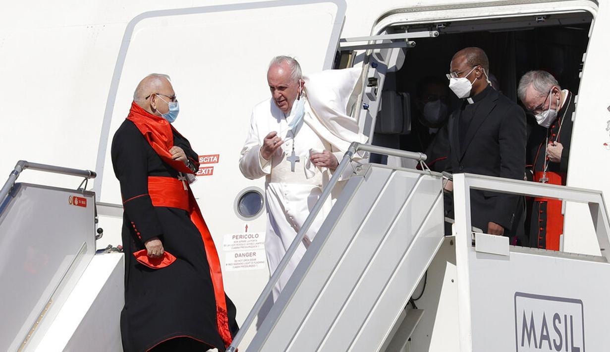 Paus Fransiskus berjalan menuruni tangga pesawat saat tiba di Bandara Internasional Baghdad, Irak, Jumat (5/3/2021). Paus Fransiskus datang ke Irak untuk mendesak umat Kristen tetap tinggal dan membantu membangun kembali Irak setelah bertahun-tahun perang. (AP Photo/Andrew Medichini)