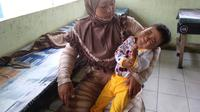 Yeni, warga Ogan Ilir Sumsel, menatap dalam wajah anaknya, Putri Ayu Anisa (4), yang mengidap penyakit komplikasi sejak usia 4 bulan (Liputan6.com / Nefri Inge)