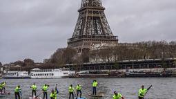 Peserta menyeberangi sungai Seine dekat menara Eiffel selama Nautic Paddle Race di Paris, Minggu (9/12). Sekitar 800 orang mengikuti lomba dayung sambil berdiri terbesar di dunia sejauh 11 km dengan pemandangan kota Paris. (Lucas BARIOULET/AFP)
