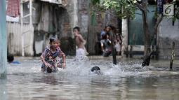 Anak- anak bermain saat banjir menggenangi kawasan Rawa Terate, Cakung Jakarta, Rabu (30/1). Banjir yang mencapai ketinggian pinggang orang dewasa terjadi sejak dini hari. (merdeka.com/Iqbal S. Nugroho)