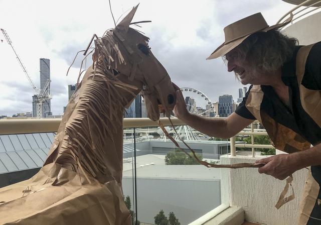 David Marriott berpose dengan kuda kertasnya Russell di kamar hotelnya di Brisbane, Australia, 3 April 2021. Direktur seni di iklan TV itu juga membuat pakaian koboi, celana topi dan juga rompi kantong kertas makanannya yang dikirimkan selama menjalani karantina. (David Marriott via AP)