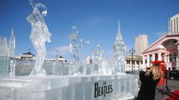 Dubes Inggris Katrin Arnold mengambil gambar patung es the Beatles dan Big Ben London di Ulaanbaatar, Mongolia (23/1). Patung dibuat untuk menandai ulang tahun ke-55 pembentukan hubungan diplomatik antara kedua negara. (AFP Photo/Byambasuren Byamba-Ochir)