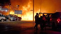 Polisi mencoba mengamankan bisnis setelah pengunjuk rasa membakar sebuah kantor di Kenosha, Wisconsin, Amerika Serikat, Senin (24/8/2020). Protes dipicu oleh penembakan Jacob Blake oleh petugas polisi Kenosha sehari sebelumnya. (AP Photo/David Goldman)