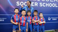 Ronaldinho berfoto bersama dengan sejumlah pemain sepak bola cilik saat peluncuran akademi sepak bola di China (24/2). Dalam peresmian akademi sepak bola tersebut Ronaldinho ditunjuk sebagai salah satu duta dari Barcelona. (Handout / Mission Hills / AFP)