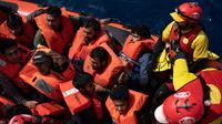 Wajah pengungsi dan imigran saat diselamatkan LSM Proactiva Open Arms Spanyol di utara pantai Libya, Minggu (6/5). Mereka berasal dari Bangladesh, Mesir, Nigeria, Marrocos, Gana, Pakistan, Sudan, Libya, Eritrea, dan Senegal. (AP Photo/Felipe Dana)