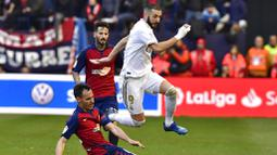 Striker Real Madrid, Karim Benzema, berusaha melewati pemain Osasuna pada laga La Liga di Stadion El Sadar, Minggu (9/2/2020). Real Madrid menang 4-1 atas Osasuna. (AP/Alvaro Barrientos)