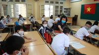 Seorang guru memeriksa suhu murid-muridnya sebelum memulai kelas di sekolah menengah Dinh Cong di Hanoi pada hari Senin. Siswa di seluruh Vietnam kembali bersekolah setelah tiga bulan belajar online. (Hau Dinh / AP)