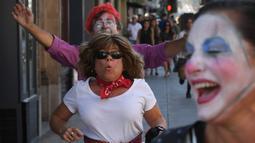 Seorang wanita berlari ketika dikejar badut dalam acara 'Running of the Clowns' di Pasadena, California pada 21 Oktober 2018. Lari dikejar kawanan badut ini merupakan parodi yang mengolok-olok lomba dikejar banteng di Pamplona, Spanyol. (Mark RALSTON/AFP)