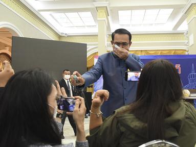 Perdana Menteri (PM) Thailand, Prayuth Chan-ocha menyemprot cairan disinfektan kepada barisan depan wartawan di ruang konferensi pers di Government House di Bangkok, Selasa (9/3/2021). Prayuth merasa terganggu saat wartawan mencecarnya dengan berbagai pertanyaan soal reshuffle kabinet. (AP Photo)