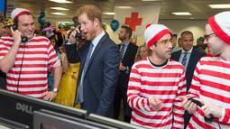 Ekspresi lucu Pangeran Harry saat ambil bagian menjadi broker dalam acara amal tahunan ICAP di London, Rabu (7/12). Pangeran Harry menjadi broker dadakan untuk mengumpulkan dana amal dari 60 kantor di seluruh dunia. (REUTERS/Geoff Pugh/Pool)