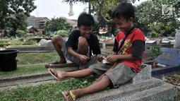 Sejumlah anak saat membagi hasil dari jasa 'Ngoret' makam di TPU Cipinang Baru, Jakarta, Minggu (5/5). Anak-anak 'Pengoret' makam mengaku dapat mengantongi uang hingga Rp 70 ribu dari hasil ngoret yang dimulai pagi sampai sore. (merdeka.com/Iqbal S. Nugroho)
