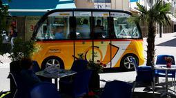 Sejumlah penumpang berada didalam angkutan umum tanpa kemudi dan sopir di Sion, Swiss, Kamis (23/6). Angkutan umum listrik pertama buatan PostAuto Schweiz ini memiliki 11 kursi penumpang dengan kecepatan maksimal 20 km per jam. (REUTERS/Ruben Sprich)