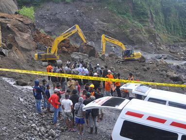 Petugas dibantu alat berat berusaha mencari korban tanah longsor di Magelang, Senin (18/12). Menurut pejabat setempat, delapan penambang tewas akibat longsor di lereng gunung berapi di pulau Jawa. (AFP Photo)