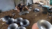 Perajin menyelesaikan pembuatan wajan yang terbuat dari pelat besi di Desa Cibadak, Tanah Sareal, Kabupaten Bogor, Jawa Barat, Rabu (5/8/2020). Pemerintah akan membantu usaha mikro, kecil, dan menengah (UMKM) dalam melewati masa pandemi COVID-19. (merdeka.com/Dwi Narwoko)