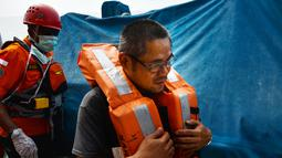 Anak buah kapal (ABK) tanker asing berbendera Bahama, Amparo Denis saat dievakuasi anggota Basarnas di lepas pantai Aceh, Selasa (30/7/2019). Basarnas Aceh mendapat informasi dari agen PT Pelni yang menyatakan ada ABK Kapal Chrysanthemum membutuhkan pertolongan medis. (CHAIDEER MAHYUDDIN/AFP)