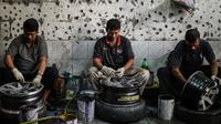 Para pekerja mencuci pelek mobil bekas sebelum menyemprotnya dengan cat di sebuah bengkel di Ampang, di pinggiran kota Kuala Lumpur, Malaysia (18/7). (AFP Photo/Mohd Rasfan)