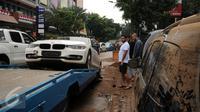 Sebuah mobil mewah dievakuasi setelah terjebak banjir di basement sebuah pertokoan di Jalan Kemang Raya, Minggu (28/8). Sejumlah kendaraan terendam air di kawasan Kemang pasca hujan deras di Jakarta, Sabtu (27/8). (Liputan6.com/Helmi Fithriansyah)
