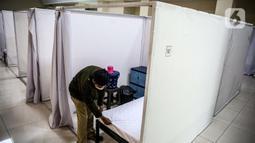 Petugas bersiap masuk ke bilik disinfektan ruang isolasi mandiri pasien COVID-19 di Gelanggang Remaja Kecamatan Pademangan, Jakarta, Senin (28/9/2020). Sebanyak 30 bilik isolasi pasien Covid-19 disediakan dengan fasilitas tempat tidur, lemari, dan peralatan mandi. (Liputan6.com/Faizal Fanani)