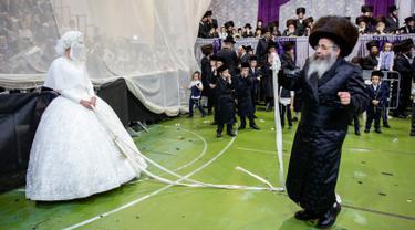 Pengantin Yahudi ultra-ortodoks Hannah Halbershtam memasuki bagian pria saat melangsungkan upacara pernikahan di kota ultra-ortodoks Bnei Brak, Israel, Selasa (20/8/2019. Dalam acara ini keluarga dan para rabi terhormat diundang untuk menari di depan pengantin wanita. (AP Photo/Oded Balilty)