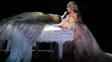 Penyanyi Lady Gaga tampil dengan piano putih berbalut sepasang sayap raksasa di panggung Grammy Awards 2018, New York,  Minggu (28/1). Bergaun baby pink yang memukau, Gaga membawakan lagu Joanne dan Million Reasons. (KEVIN WINTER/GETTY IMAGES/AFP)