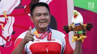 Atlet ParaCycling, Soemantri menggigit medali perunggu nomor Mens H4-5 Individual Time Trial Road Race Asian Para Games 2018 di Sirkuit Sentul, Bogor, Senin (8/10). Soemantri berhasil merebut medali perunggu. (Liputan6.com/Helmi Fithriansyah)